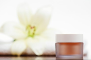Skincare cream with white flower in background.