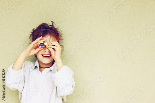 Leinwanddruck Bild Happy kid playing with binoculars. explore and adventure concept
