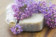 bar of natural soap, bath salt and lilac flowers