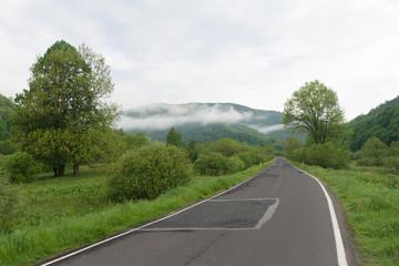 Droga asfaltowa w górach, mglisty poranek, Bieszczady