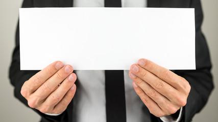 Busienssman holding blank paper