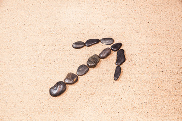 arrow drawn with pebbles on the beach sand