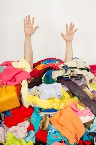 Man hands reaching out for help from a big pile of woman clothes - 65681069