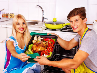 Couple cooking chicken at kitchen.
