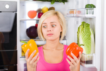 girl unhappy look red pepper, refrigerator