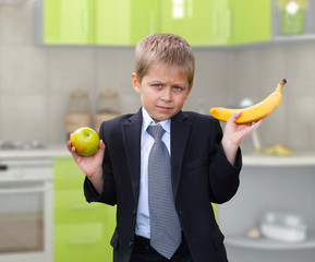 schoolboy holding apple and banana, making choices, on kitchen b