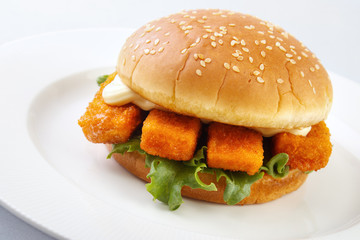 Fishburger and mayonnaise on white plate