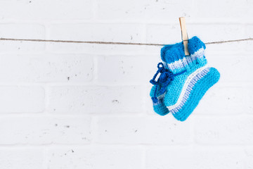 knitted baby socks hanging on clothesline against white brick wa