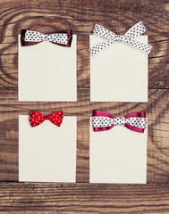 four blank paper sheets with colorful bows on wooden background