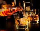 Fototapety barman pouring whiskey in front of whiskey glass and bottles
