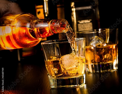 Foto op Canvas Bar barman pouring whiskey in front of whiskey glass and bottles