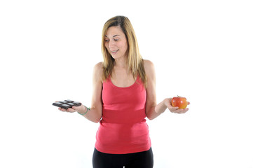 fit 40s Woman with Apple and Chocolate in Hands to choose