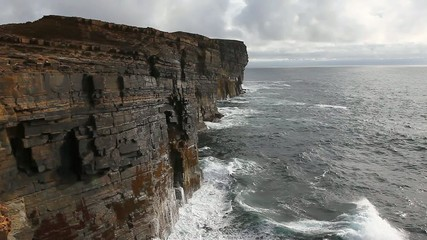 Large waves crash against rock cliffs in Orkney, Scotland