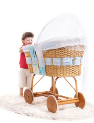 Small boy looking at baby sleeing in retro style crib