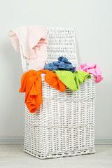 Full laundry basket on gray background