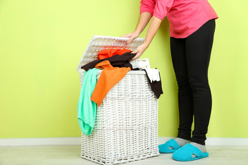 Woman with full laundry basket on green background