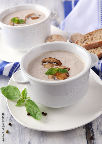 Mushroom soup in white pots, on napkin, on wooden background