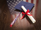 Graduation Cap, Diploma on Table with American Flag Reflection - 65694492