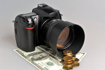 Photo camera with coins and banknotes on gray