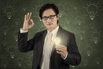 Businessman holding lightbulb and showing ok gesture