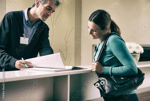 Happy female patient in 40s registering at hospital reception de - 65696445