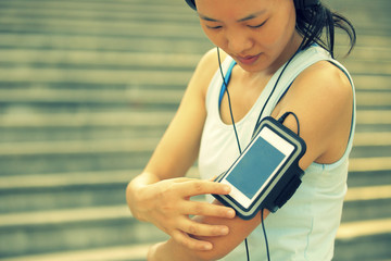 woman runner listening to music in headphones from smart phone