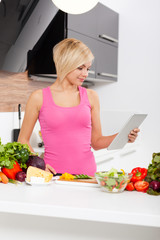 woman using a tablet computer to cook
