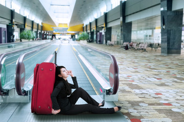 Businesswoman sitting on the floor in airport