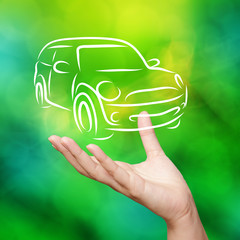Hand with car against green nature sky background as concept