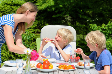 Mother and kids having barbecue lunch in the garden