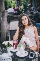 beautiful girl with a bouquet of peonies sitting in a restaurant