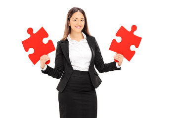 Young businesswoman holding two pieces of puzzle