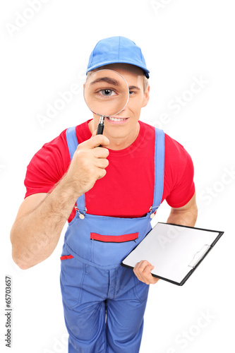 Male mechanic looking through magnifying glass