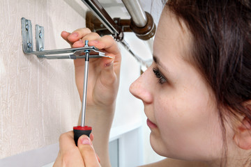 Girl fastens screwdriver bracket vertical blinds to wall.
