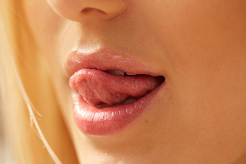 Licking young sensual moisturized lips.