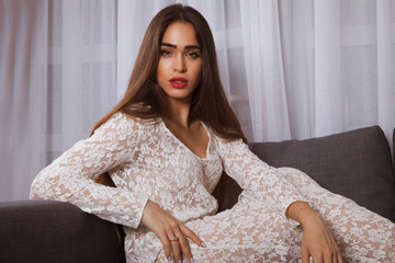 Elegant sensual young woman in lace dress on couch