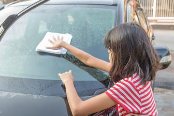Young Asian Malay girl washing car