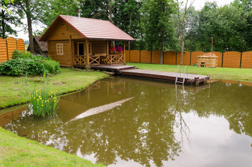 new rural bathhouse and pond with plank footbridge
