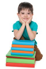 Cute young boy near books
