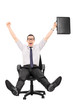 Happy businessman riding in an office chair