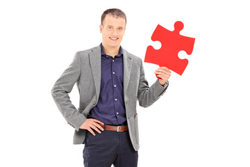 Elegant man holding a piece of puzzle