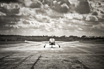 sepia toned light aircraft take-off into dark clouds