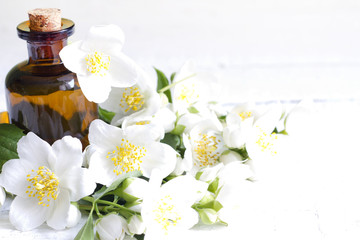 Jasmine aromatherapy oil on white planks with flowers