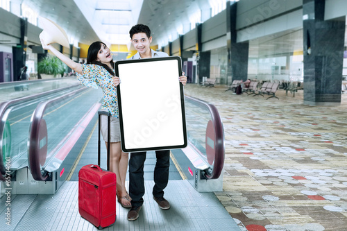 Excited tourists holding billboard