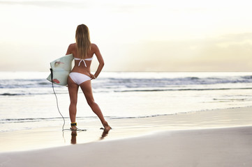 Young attractive surfer at the beach with surfboard