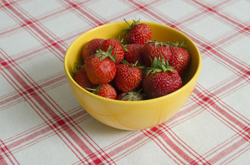strawberries in a yellow bowl on cloth background
