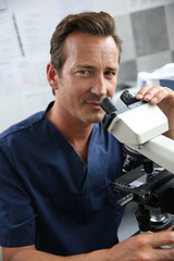 Doctor in laboratory looking through microscope