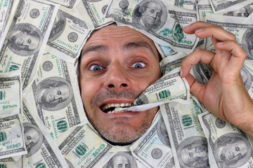 man under a bed of dollars