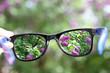 Leinwanddruck Bild - eyeglasses in the hand over blurred background