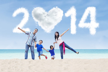 Happy family celebrate new year 2014 in the beach